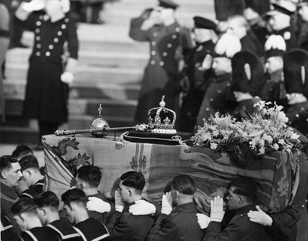 GettyImages-3402504 The coffin of George VI draped with the royal standard being carried by soldiers. On the top are symbols of royalty, a crown, sceptre and orb. (