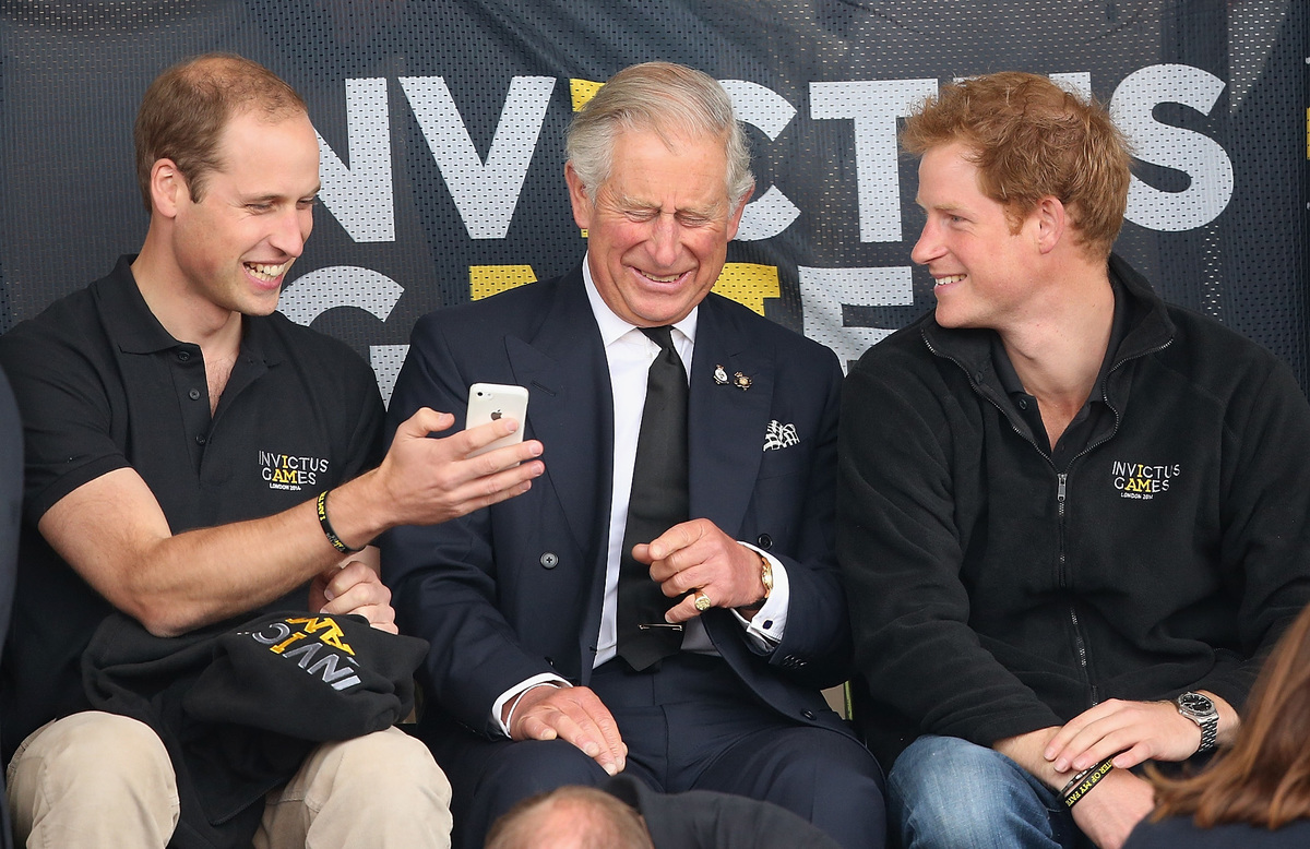 Prince William, Duke of Cambridge, Prince Harry and Prince Charles, Prince of Wales look at a mobile phone as they watch the athletics at Lee Valley Track during the Invictus Games on September 11, 2014 in London, England.