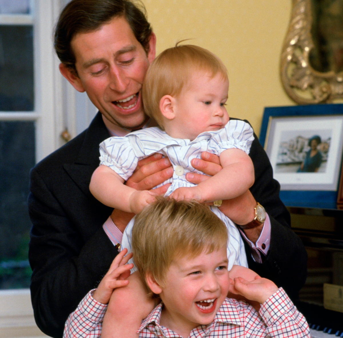 Prince Charles Laughing With His Sons As He Lifts Prince Harry Onto Prince William's Shoulders In Kensington Palace.