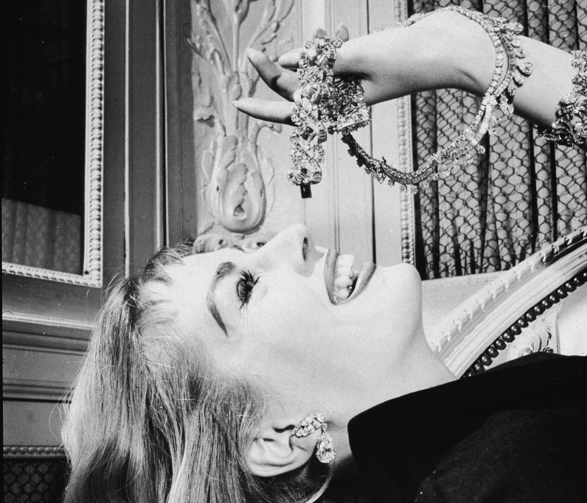 Swedish-born actress Anita Ekberg mimics the pose of eating grapes with pieces of diamond Cartier jewelry