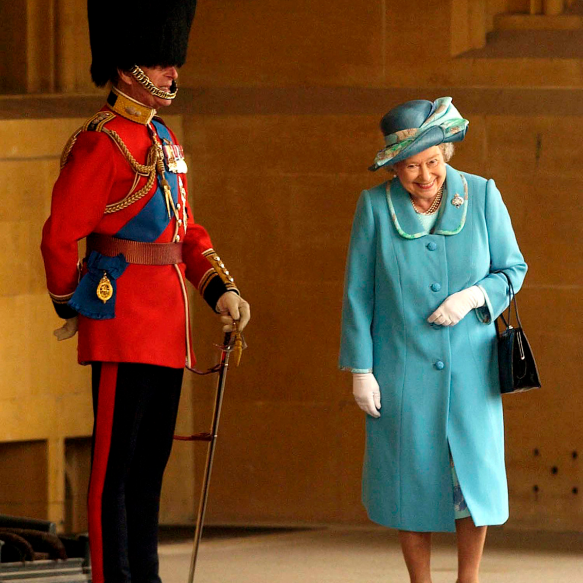Queen Elizabeth II gets a fit of the giggles as she walks past her husband Prince Philip, the Duke of Edinburgh who is standing to attention in his uniform and bearskin hat at Buckingham Palace in 2005.
