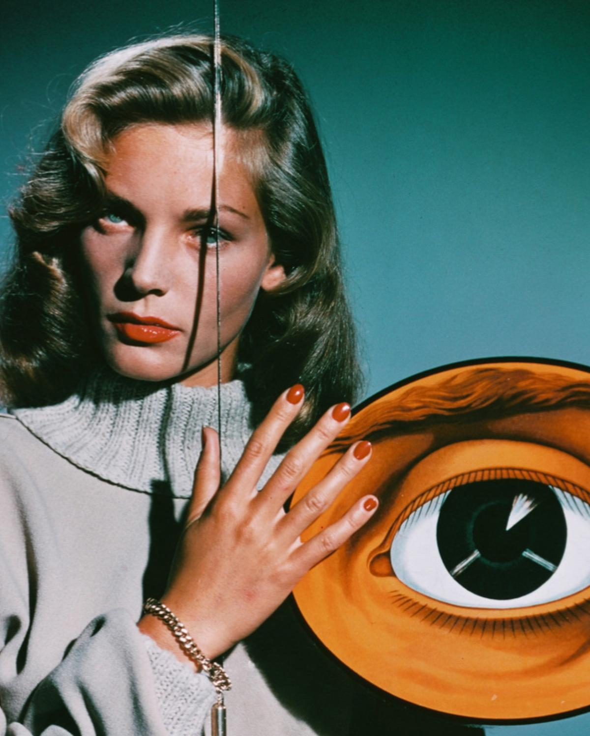 American actress Lauren Bacall poses behind a pane of glass decorated with two giant eyes, circa 1950.