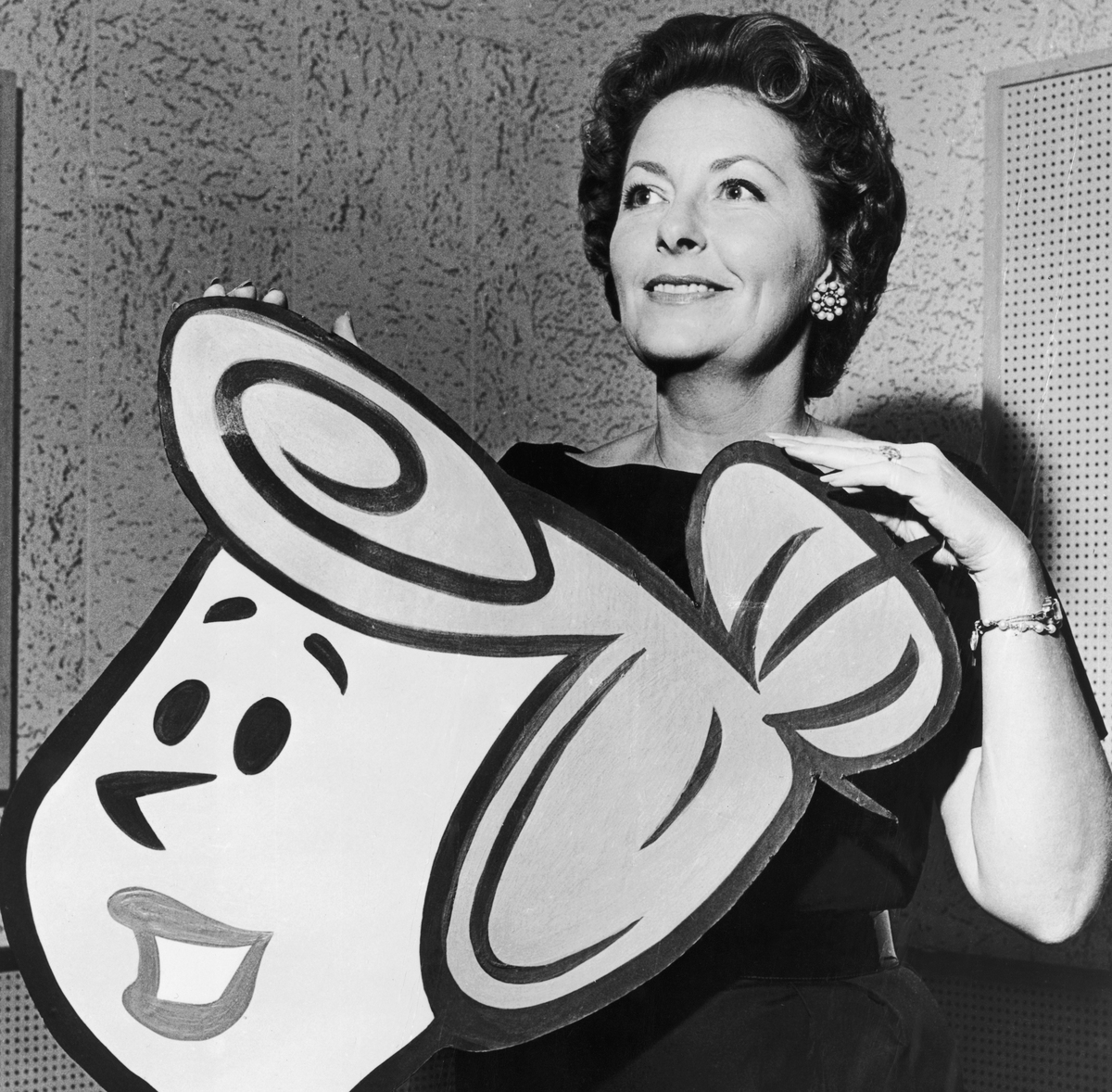 American actress Jean Vander Pyl poses with a cardboard cut-out of Wilma Flintstone, whose voice she provides
