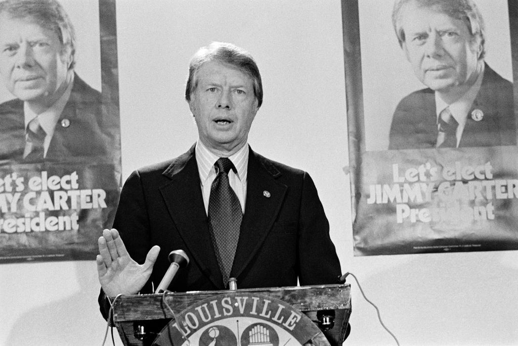 Louisville, Kentucky, USA - November 23, 1975: Then Governor of Georgia, Jimmy Carter stands in front of posters saying 'Let's Elect JIMMY CARTER President' and addresses the National Democratic Issues Convention.