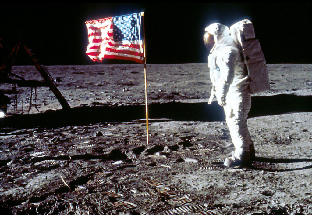 buzz aldrin in a space suit standing on the moon with a backwards american flag