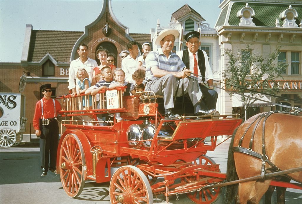 walt disney and other disneyland guest on top of a horsedrawn fire wagon