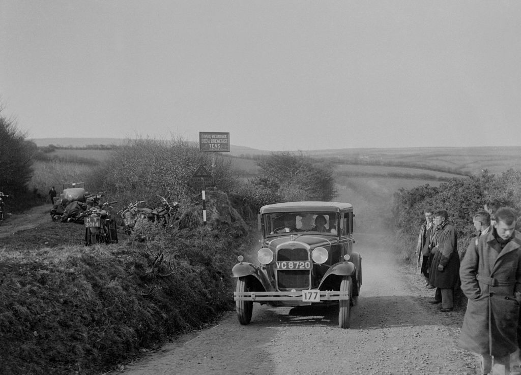 black and white photo of people driving a ford model a along a dirt road with bystanders and bikes on the side