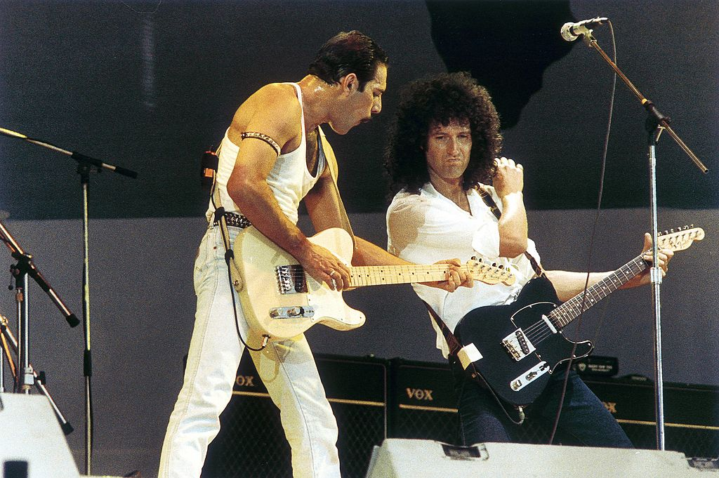 freddie mercury and brian may of queen performing on stage at live aid