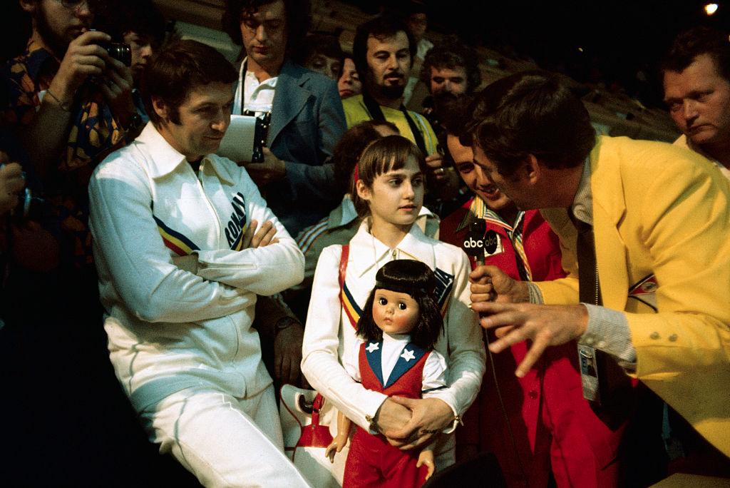 nadia comaneci holding a doll while being interviewed at the olympics