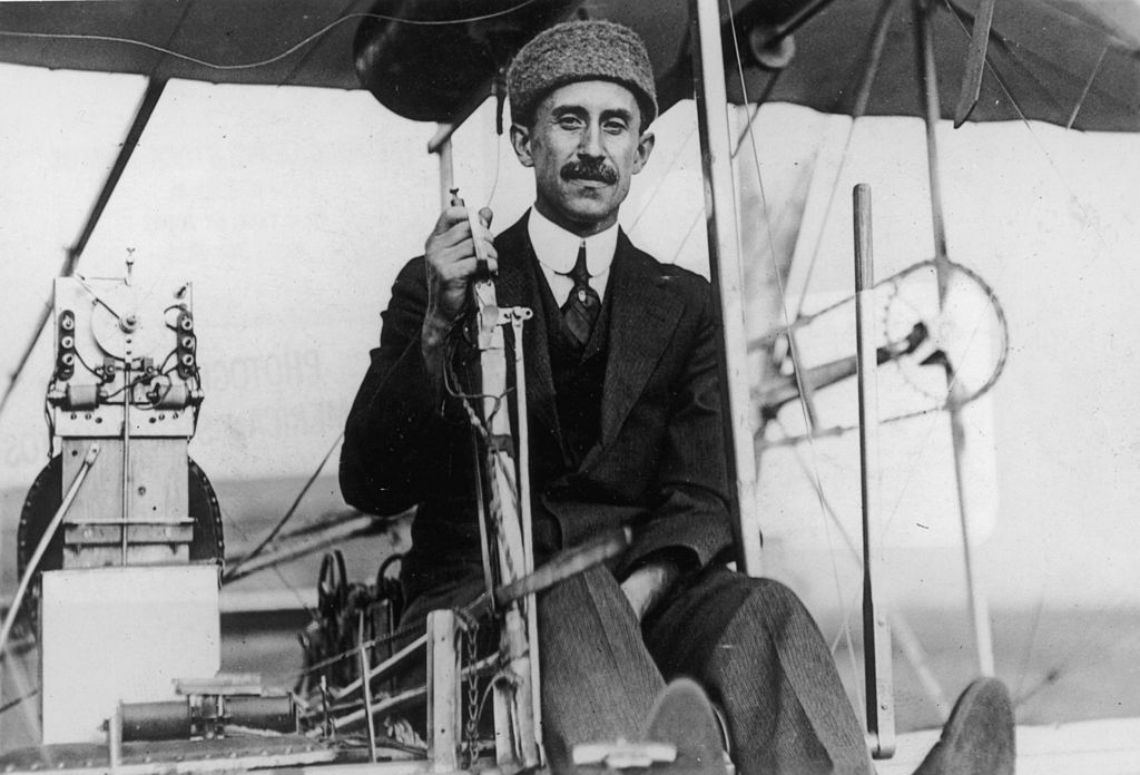 orville wright sitting in one of his biplanes dressed in a three-piece suit and a cap