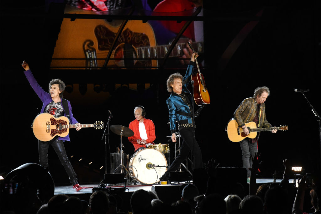 the rolling stones: ronnie wood, charlie watts, mick jagger, and keith richards performing on stage