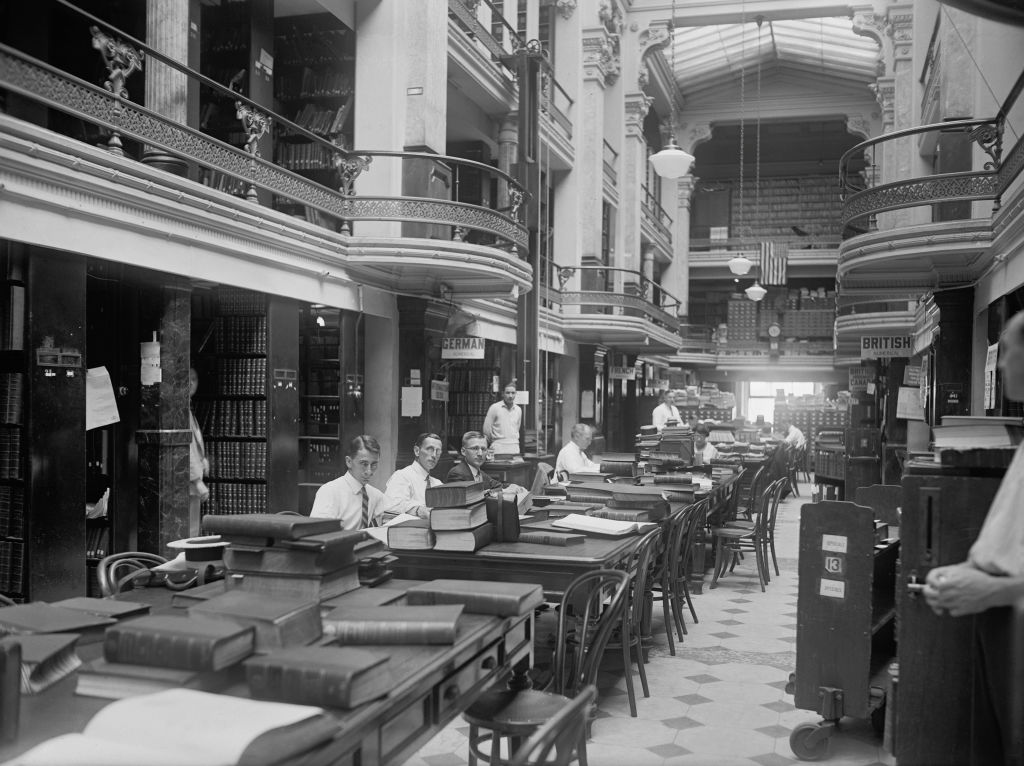 men sitting in the us patent office with large books on the tables
