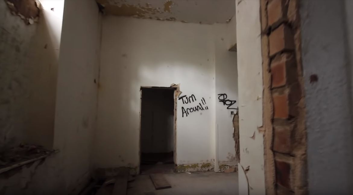 empty doorway and graffiti in the abandoned Denbigh Asylum