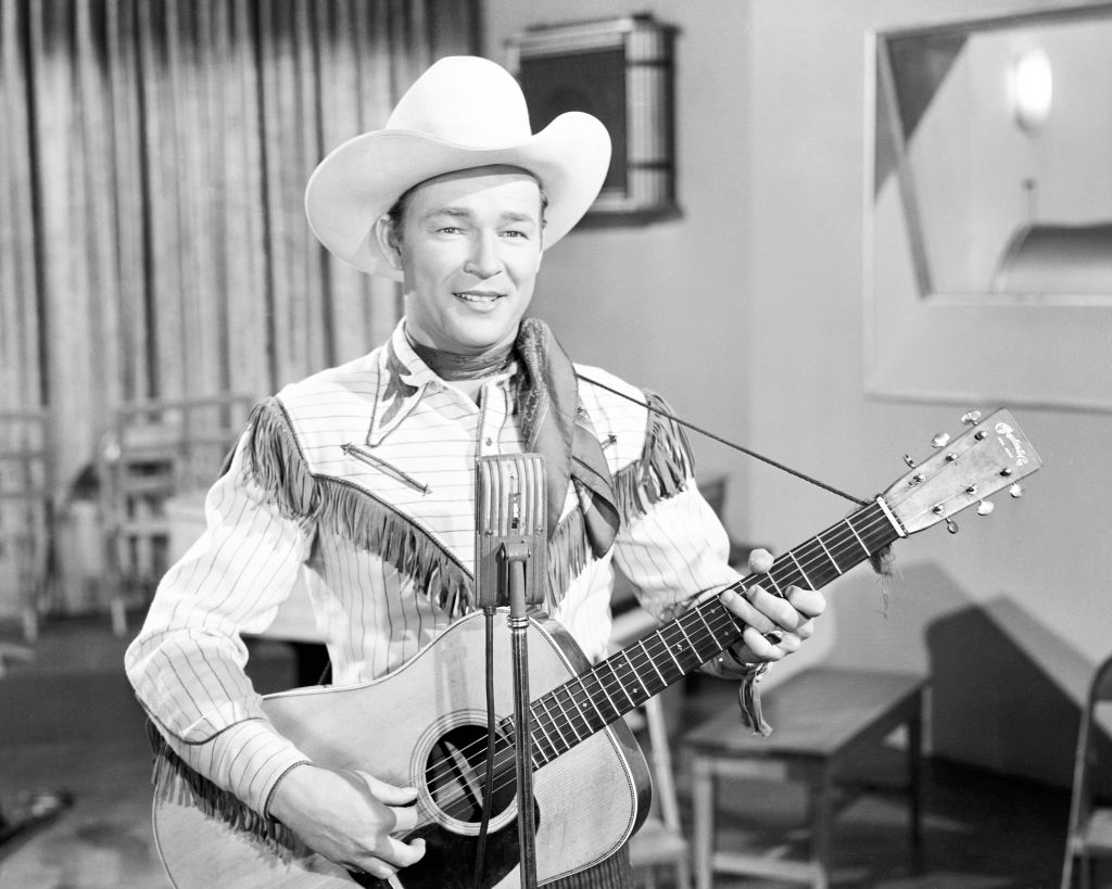 American singer and cowboy actor Roy Rogers (1911 - 1998) playing an acoustic guitar,