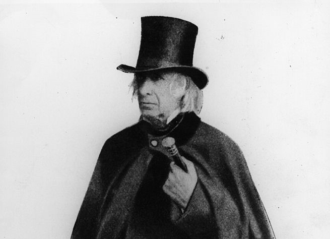 Amos Bronson Alcott wears a heavy overcoat and a tophat while posting for a portrait in 1882.