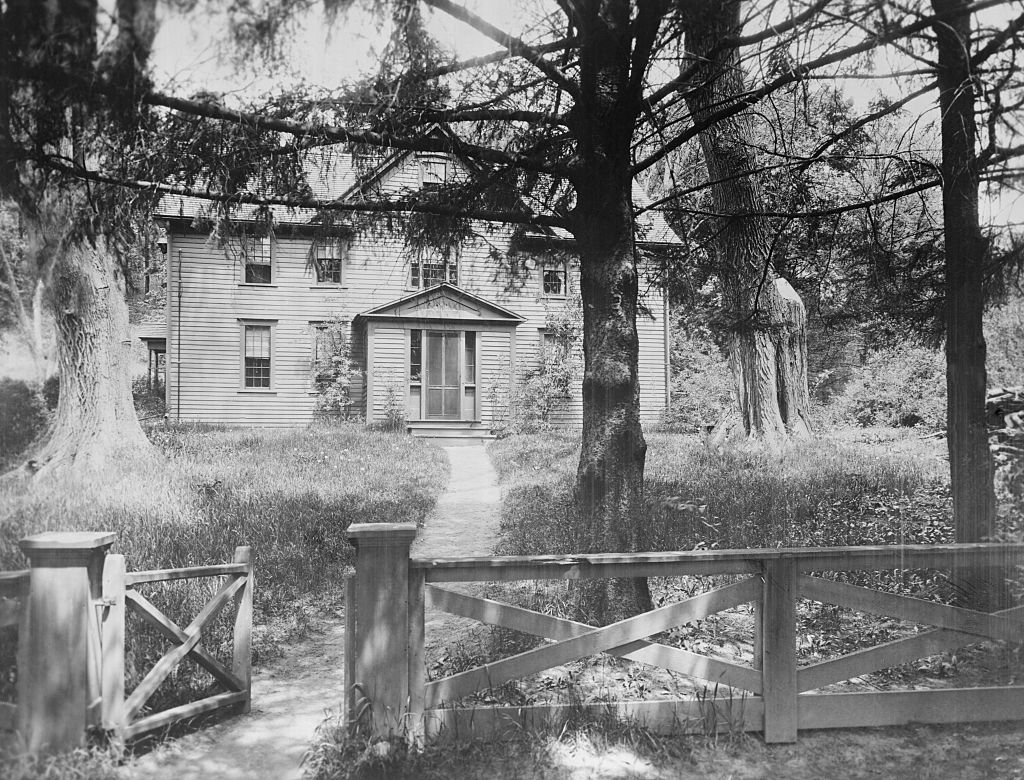 The Alcott family's wooden Orchard House is pictured in balck and white, surrounded by trees and a fence.