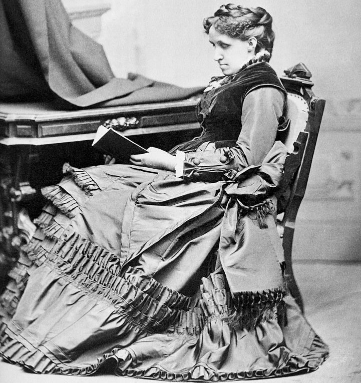 Louisa wears a thick, ruffled gown while reading at a desk.