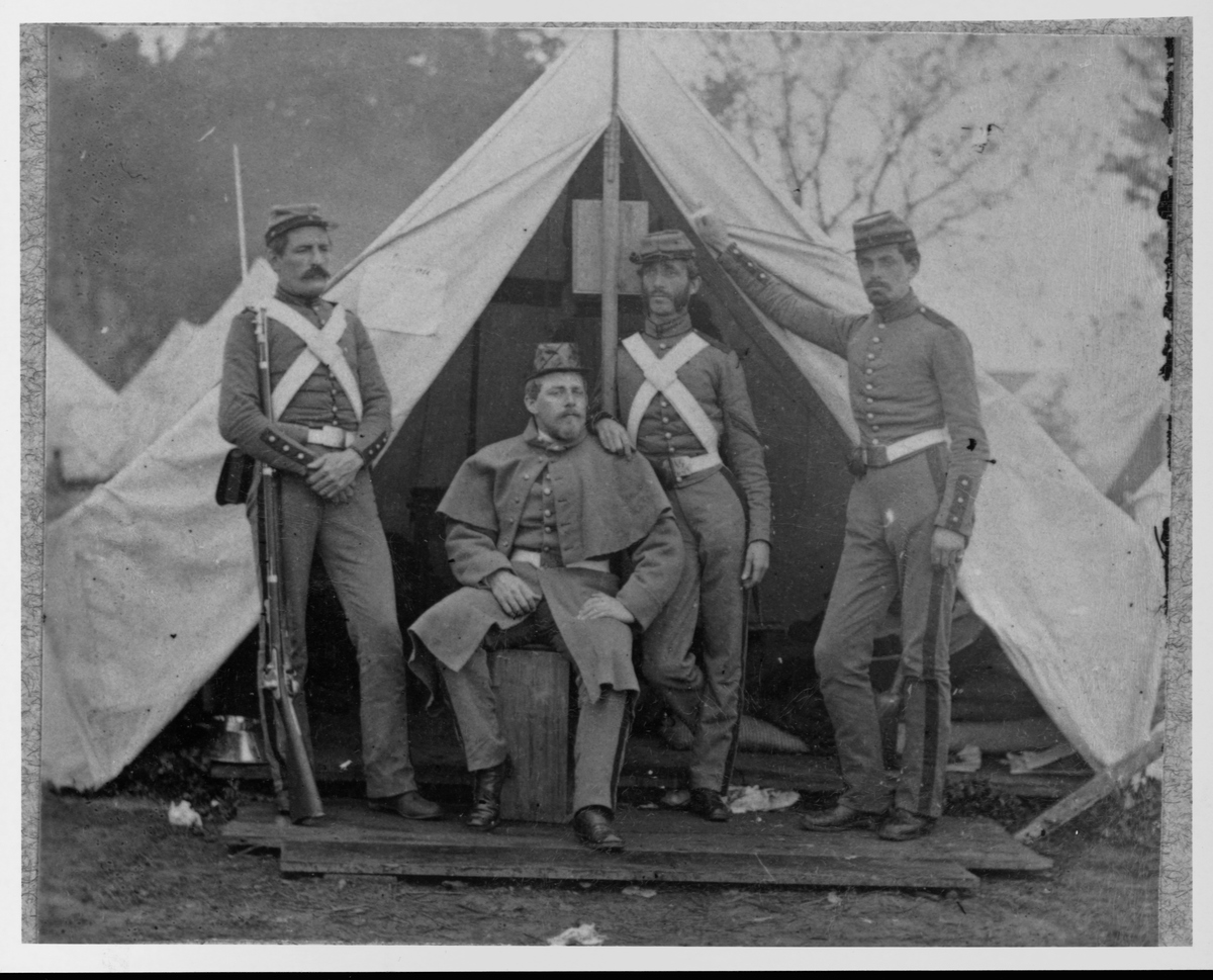 Civil War soldiers of the 7th New York State Militia by tent opening in Camp Cameron, Washington, DC.