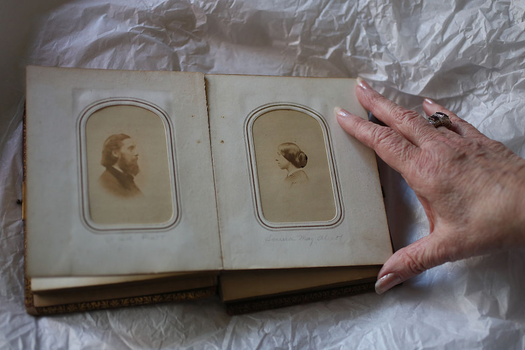 An old Alcott family photobook is held open to reveal a portrait of John Bridge Pratt facing a separate portrait of Anna Alcott Pratt.