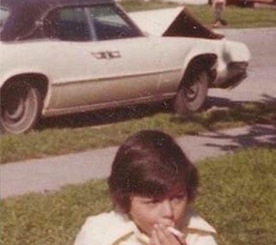 kid smoking cigarette outside crashed car