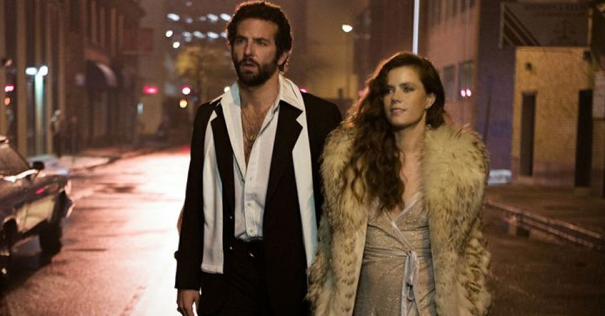 bradley cooper and amy adams walking on the street in 70s clothes in american hustle
