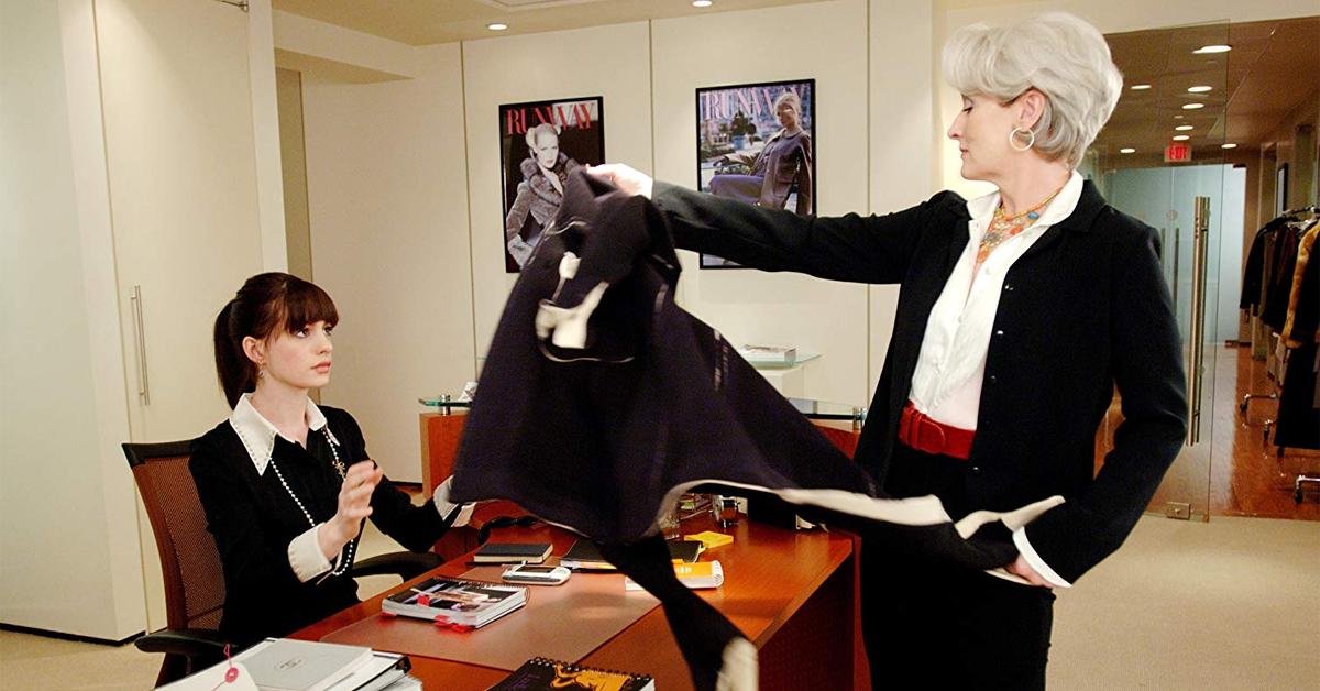 meryl streep handing a jacket to anne hathaway in the devil wears prada