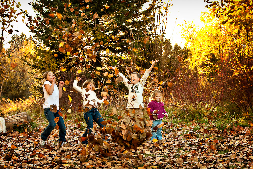 Four small children throw fall leaves in the air