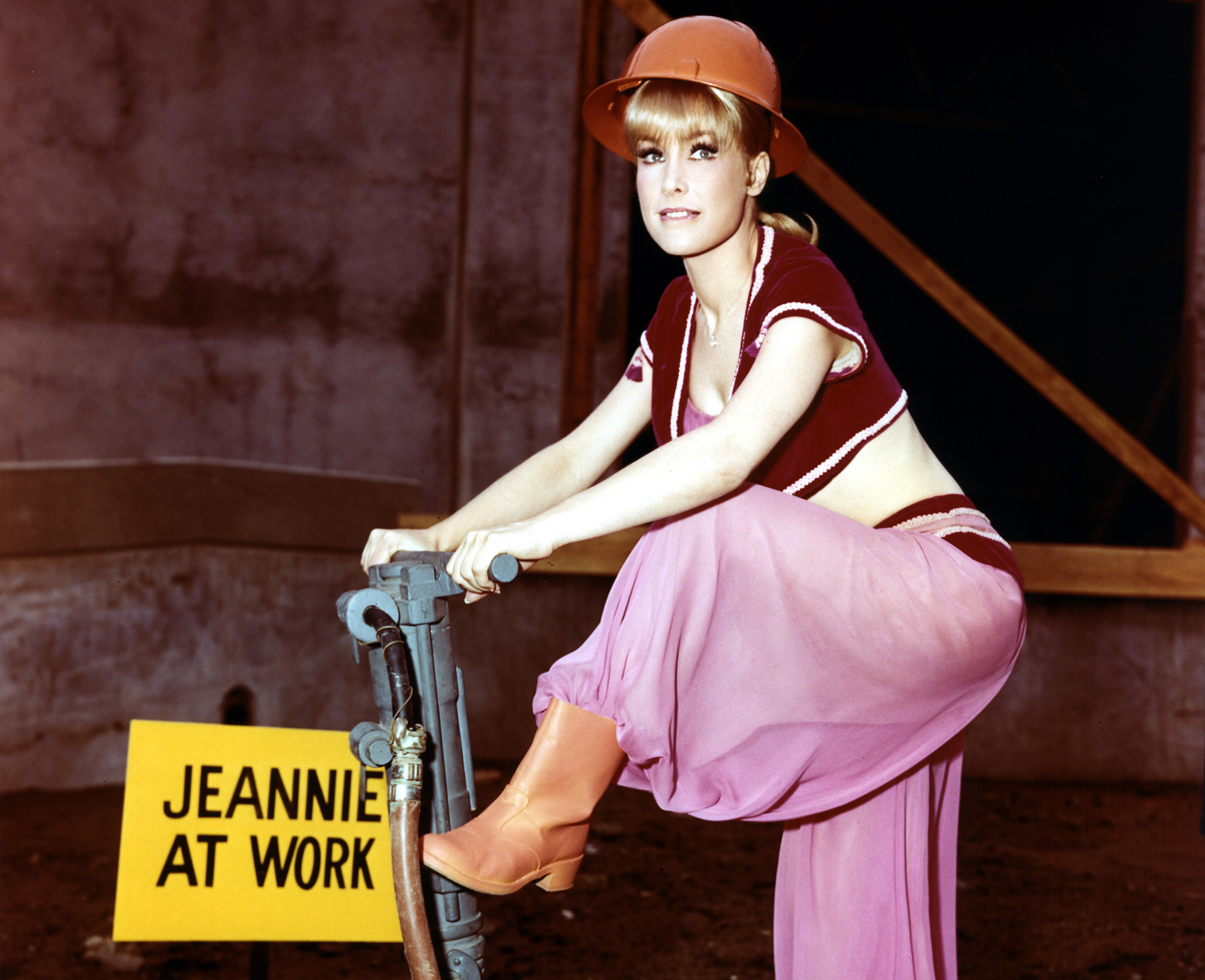 Barbara Eden, US actress, in costume, posing with a pneumatic drill and wearing a hard hat alongside a sign reading 'Jeannie at work'