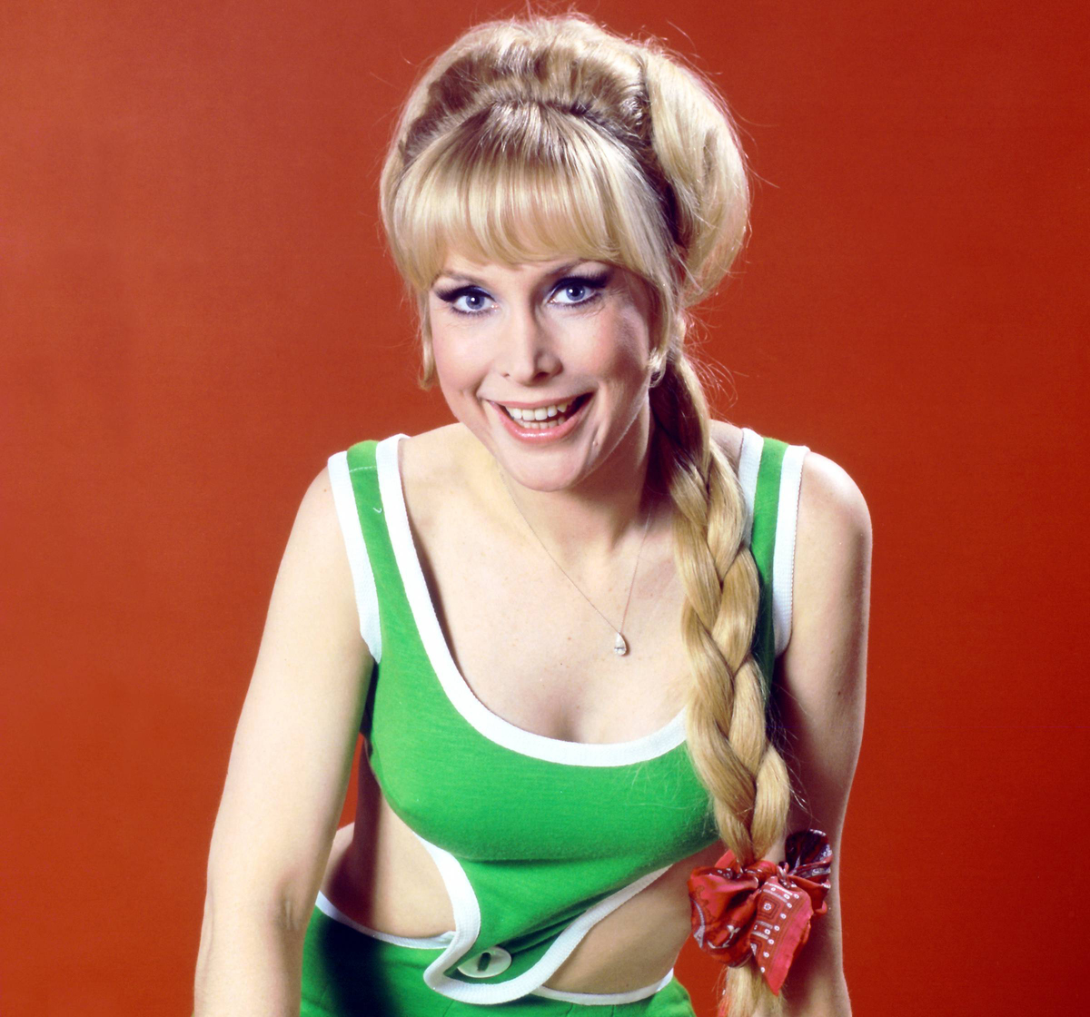 Barbara Eden, US actress, wearing a green and white outfit, smiling with her hair plaited, with a red bow, in a studio portrait, against a red background, circa 1965.