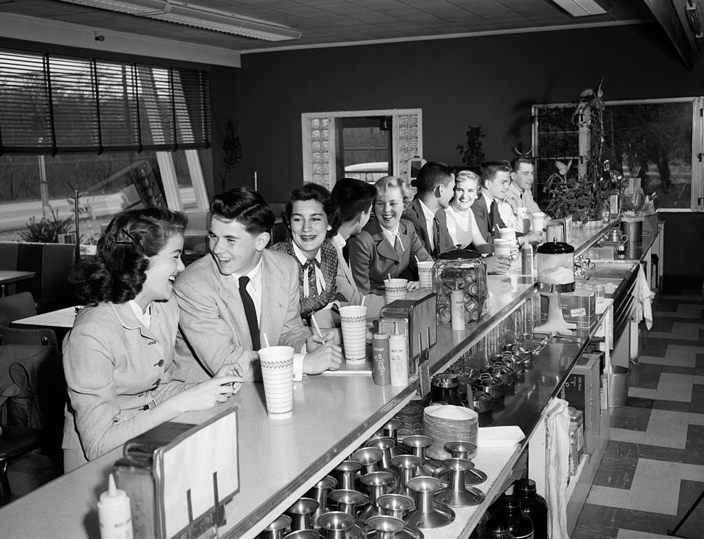 Teens sitting at a soda fountain bar