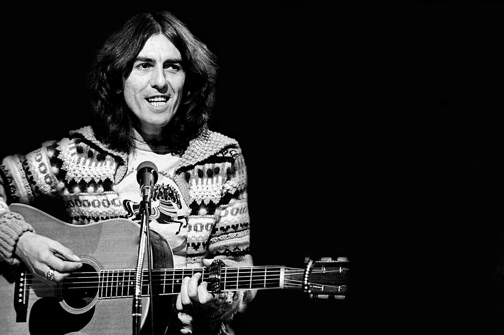 George Harrison playing guitar in a sweater