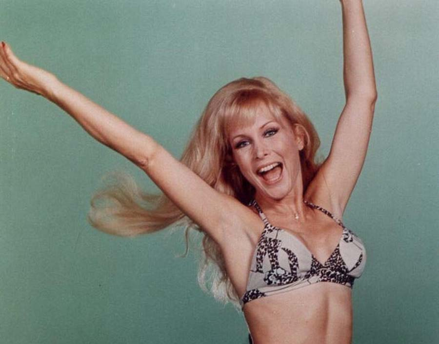 Barbara Eden in a bikini throwing her hands up