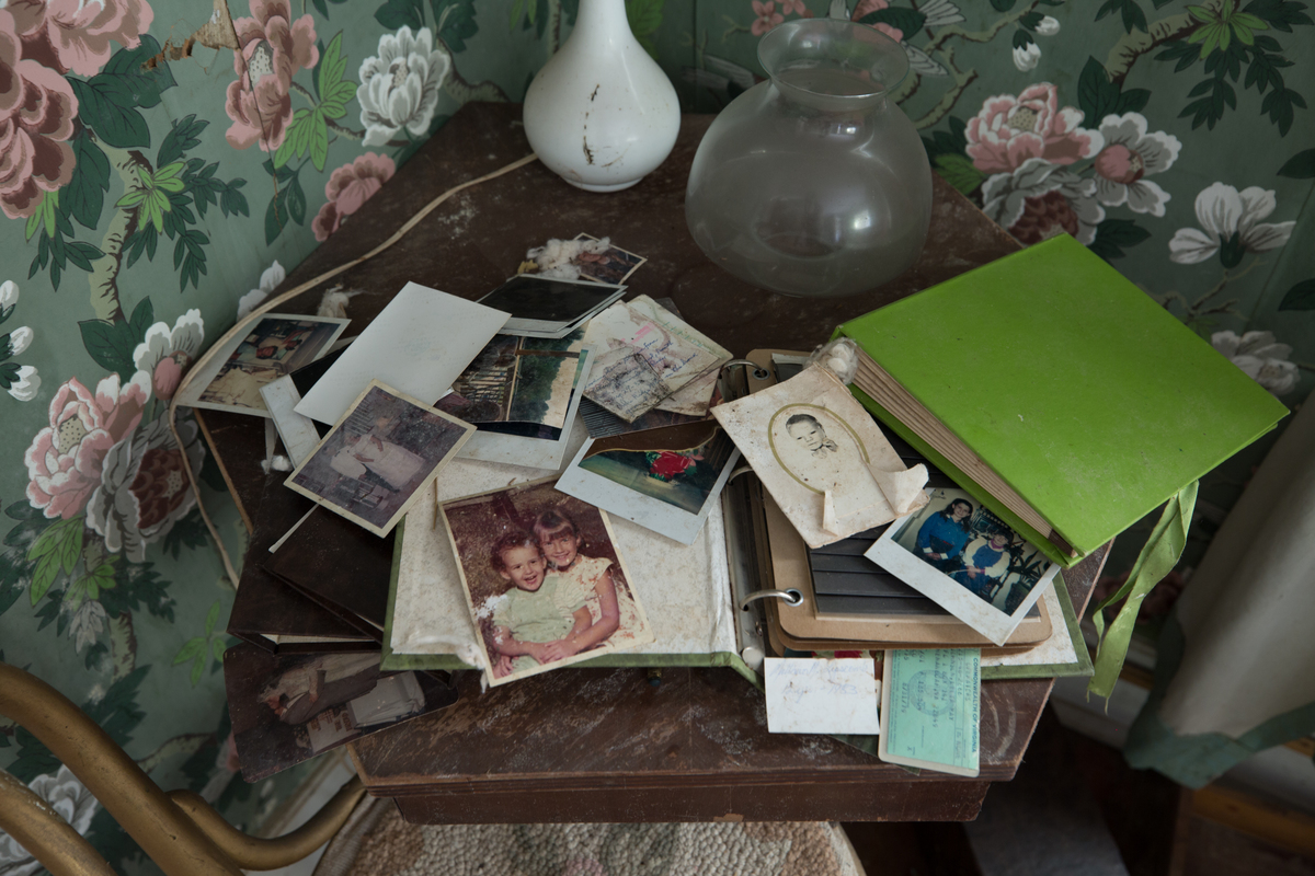 Old photos and photo albums lie on a table.