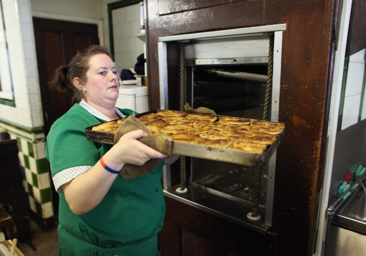 A member of staff removes a tray of freshly cooked pies from the dumbwaiter