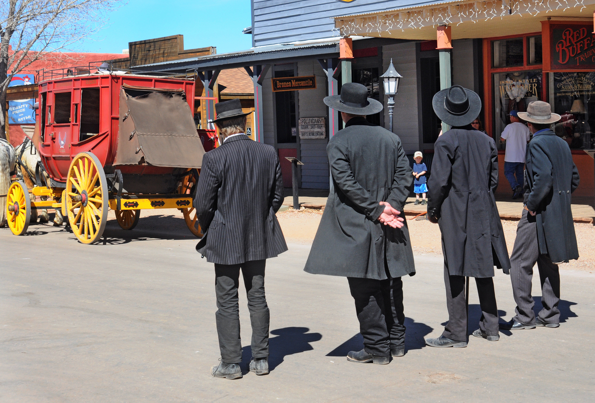 Reenactors portraying Wyatt Earp, his brothers Morgan and Virgil Earp, and Doc Holliday prepare for a gunfight in historic Tombstone, Arizona.