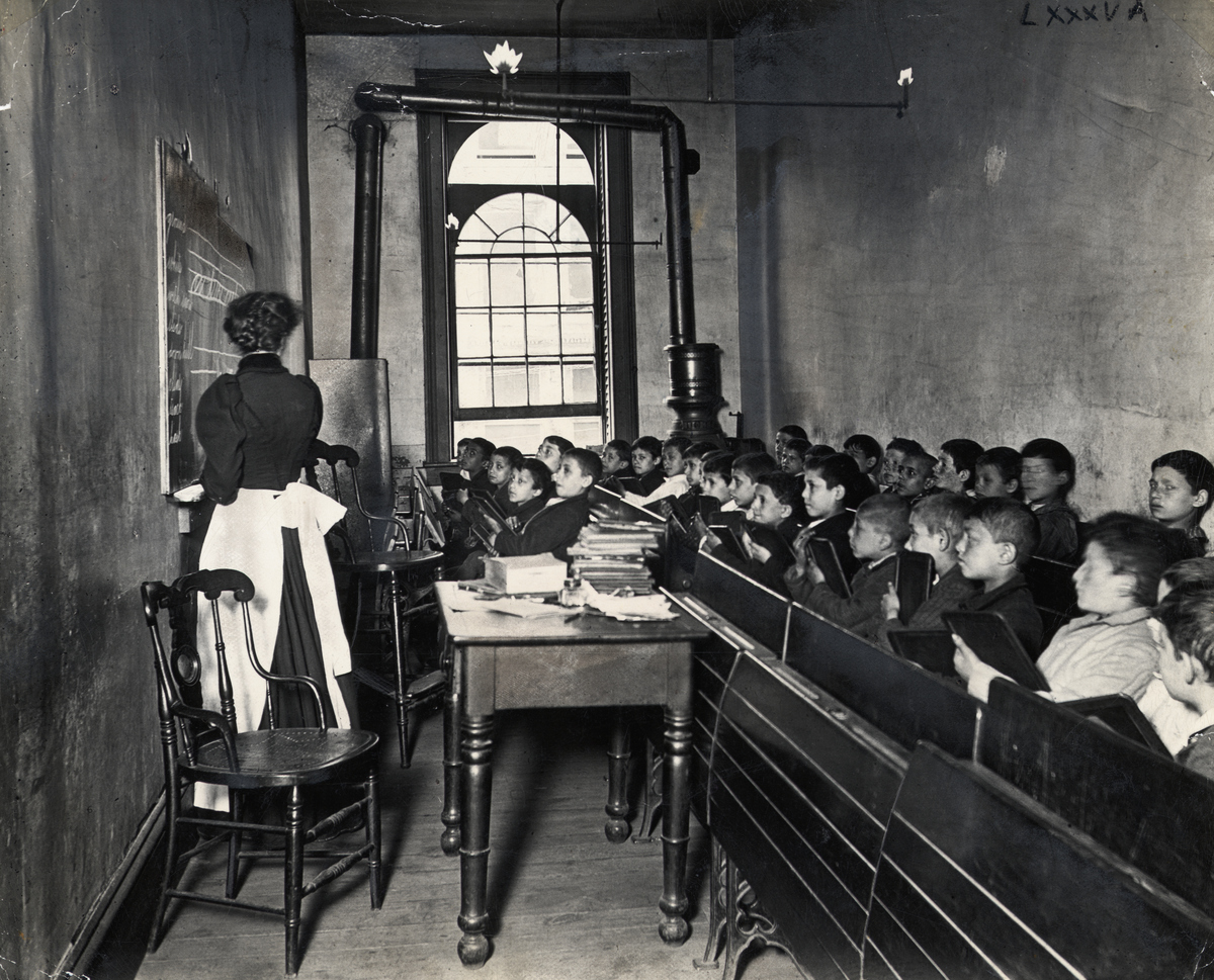 A teacher demonstrates on the blackboard, as students watch attentively from crowded pews, circa 1886