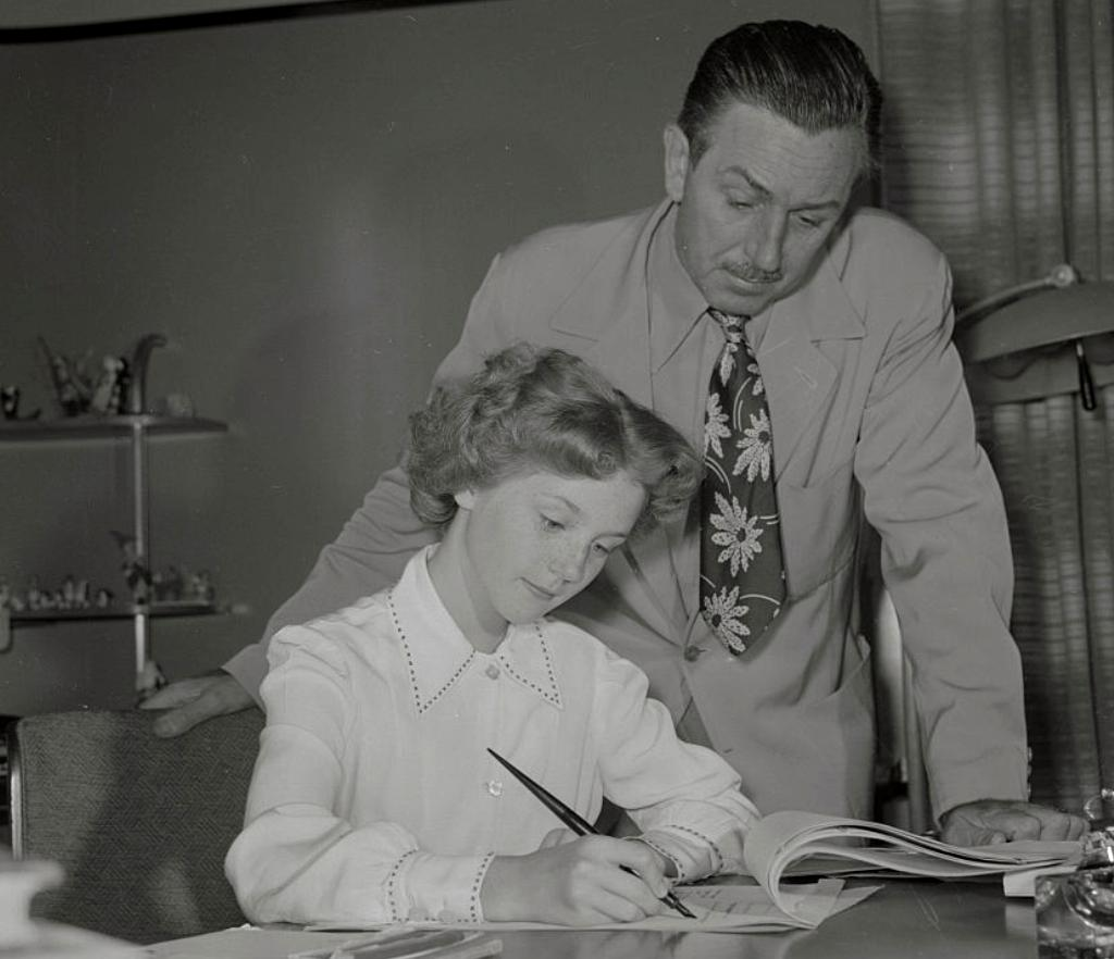 Walt Disney looks over her shoulder as a young Kathrym Beaumont signs her contract