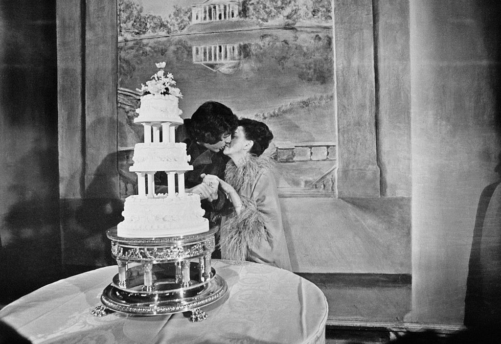 kissing in front of wedding cake