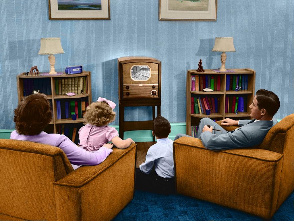 A 1950s family gathers around their tiny television set