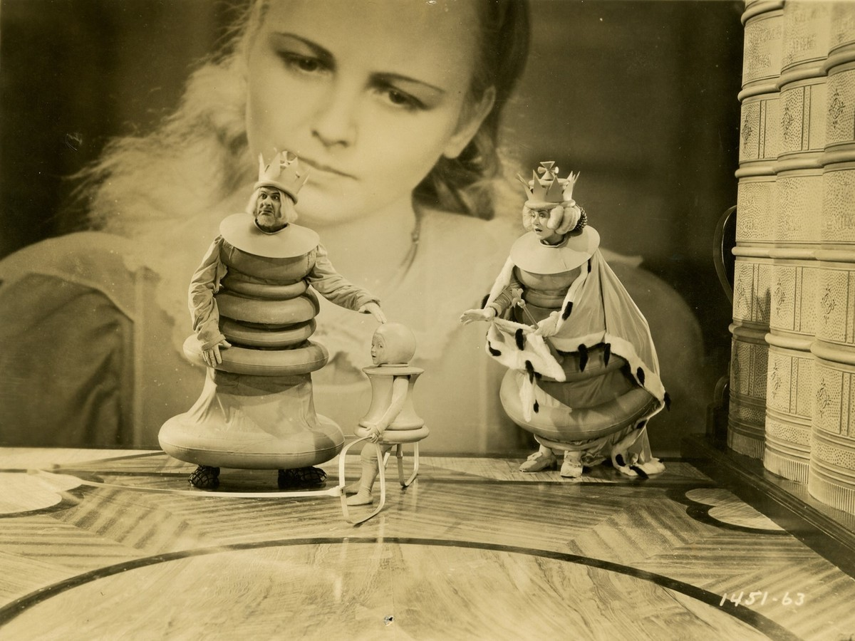 An enlarged Alice looks at tiny live-action characters in the 1933 Alice in Wonderland