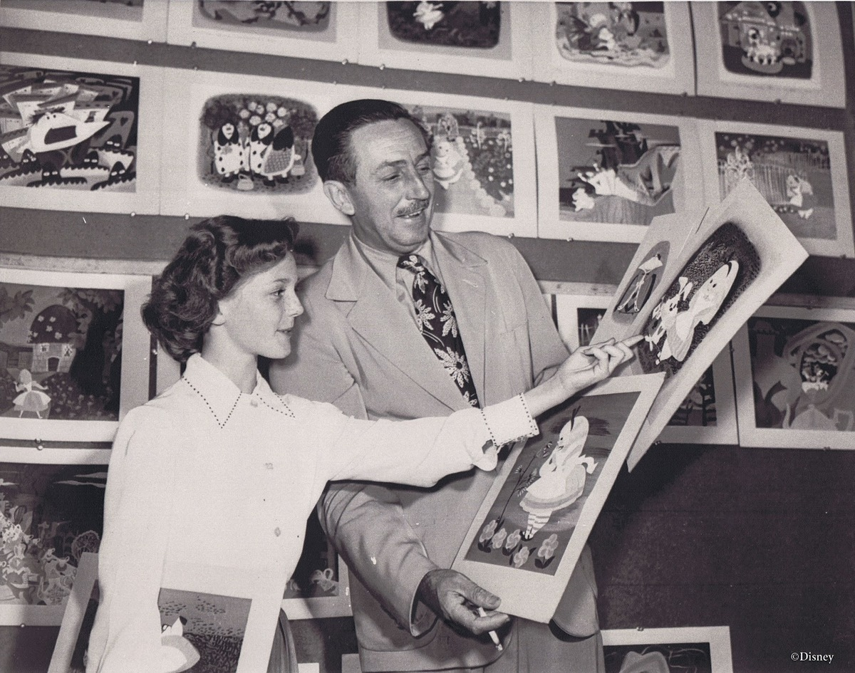 Disney holds up photos of Alice while actress Kathryn Beaumont points to them