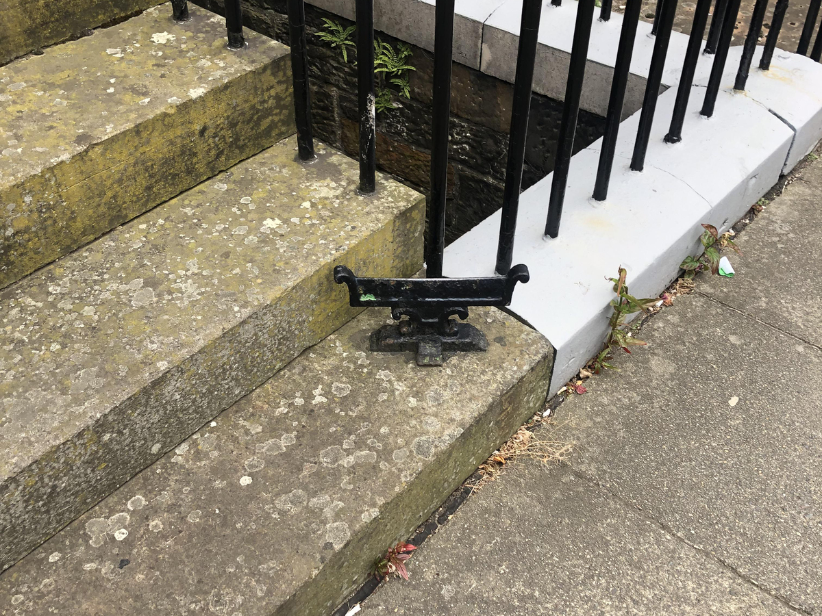 A metal boot scraper sits on the stairs of an Edinburgh home.