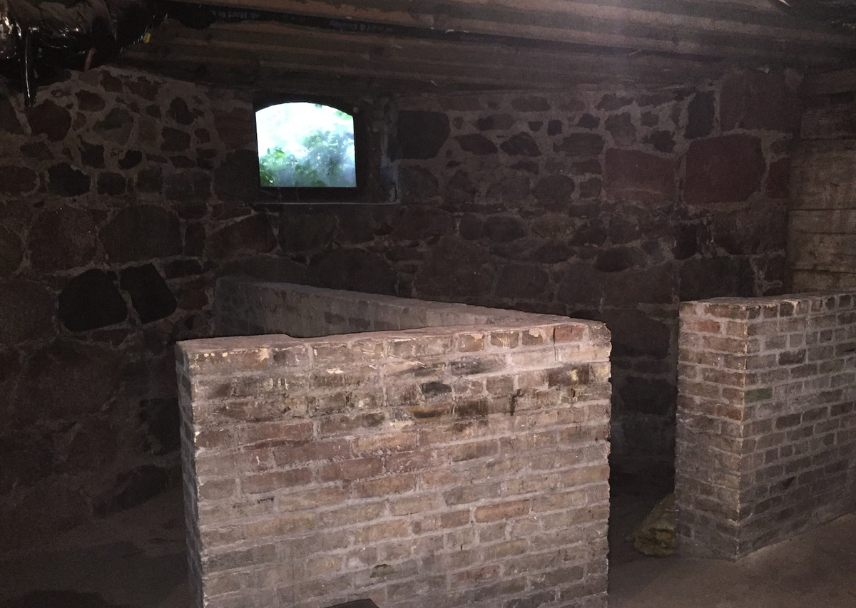 An open coal door leads to a stone basement.