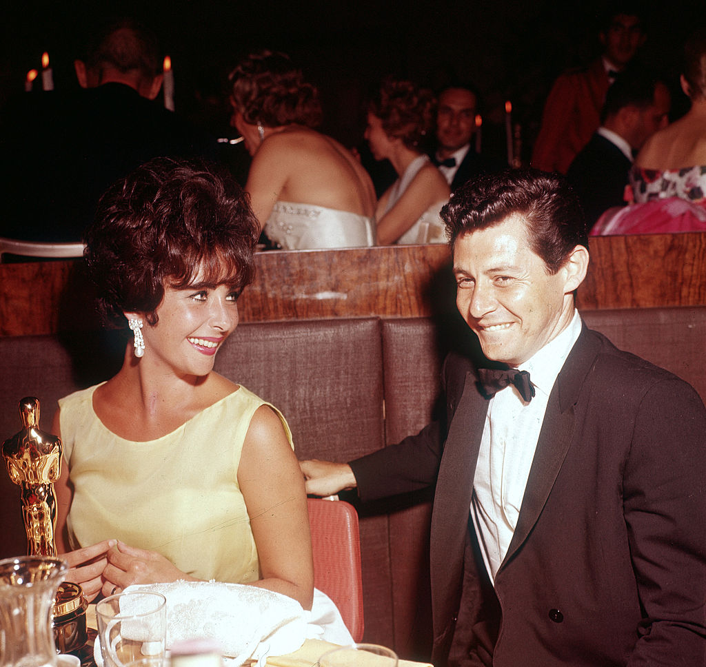 elizabeth taylor and husband eddie fisher sitting at a table with her oscar statue
