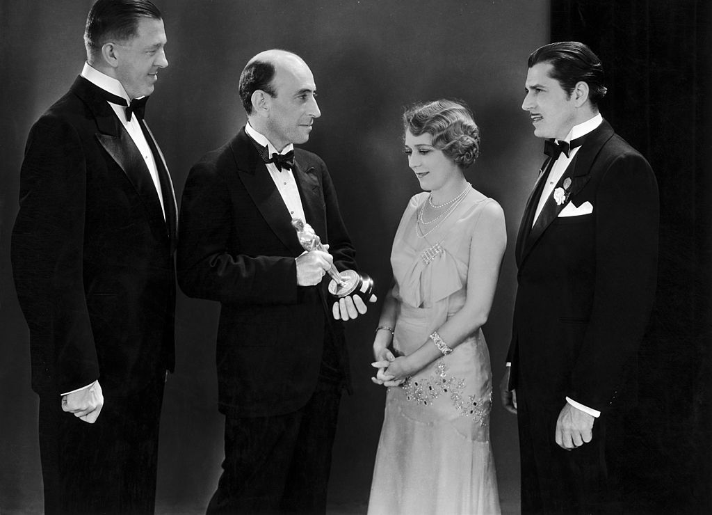 william c. demille handing an oscar to mary pickford, warner baxter, and hans kraly