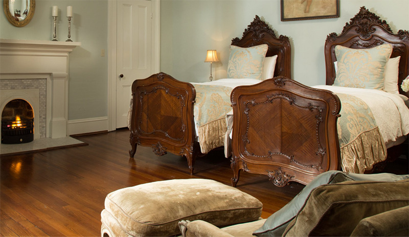 Two twin beds sit between a reading chair and a fireplace.