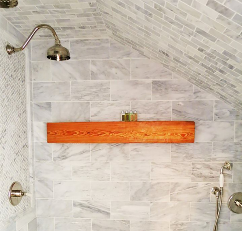 A tiled shower has an angled ceiling.