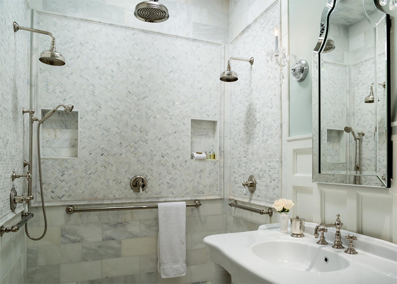 A bright bathroom features a marbel shower.