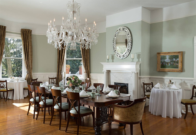 A large, formal dining room features large windows and a chandelier.