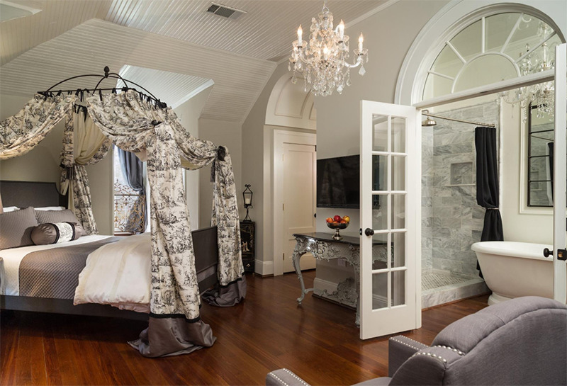 A grey and white bedroom is separated by french doors that lead to an elegant bathroom.